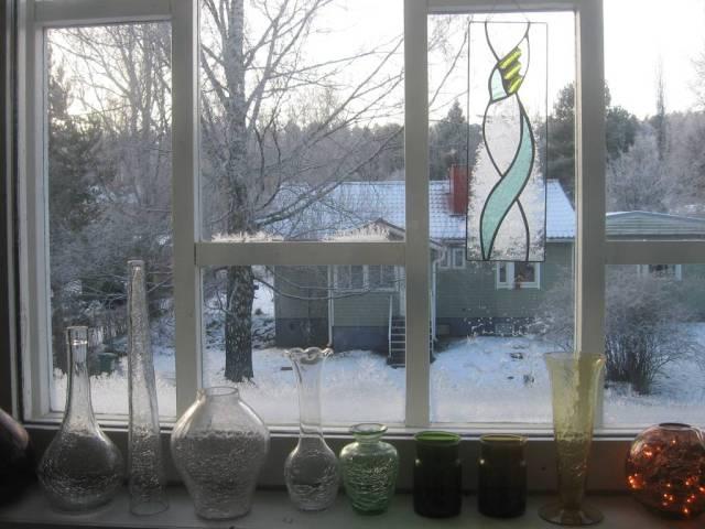 La naturaleza ha añadido sus adornos a la ventana detras de la obra pendiente de vidrio